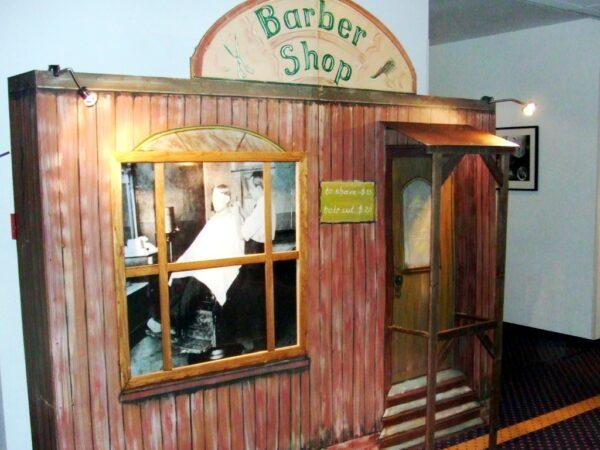 Ballonrasieren vor Western-Dekowand Barber Shop mieten